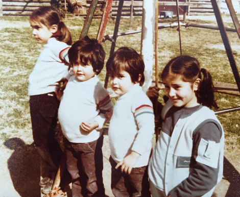 Four Locatelli children, three wearing similar hand knit sweaters