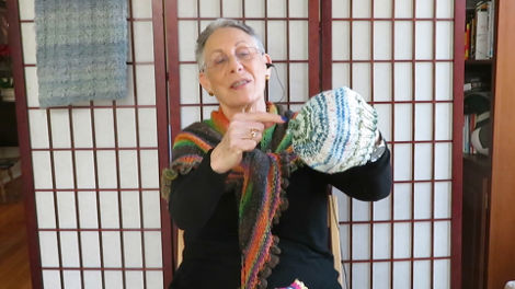 Lynn showing one of the hats knitted by an inmate through the Knitting Behind Bars program.